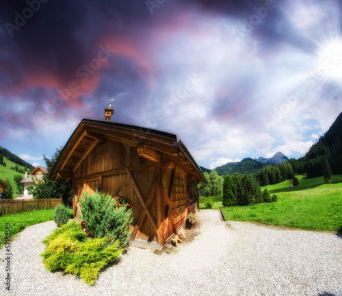 Dolomites, Italy. Beautiful sunset with wooden hut and typical v