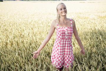 Junge Frau im Sommerkleid geht durch ein Kornfeld