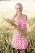 canvas print picture - Junge blonde Frau geht durch ein Kornfeld