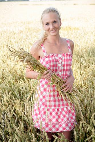 canvas print picture Junge blonde Frau geht durch ein Kornfeld