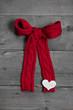 Gestrickte rote Schleife als Glückwunschkarte mit Herz auf Holz