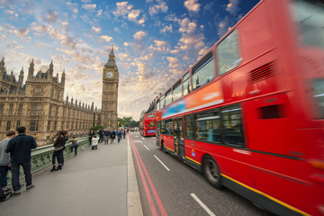 Iconic red bus passing over Westminster Bridge in London