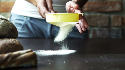 flour sifting through the strainer on the table, slow motion at