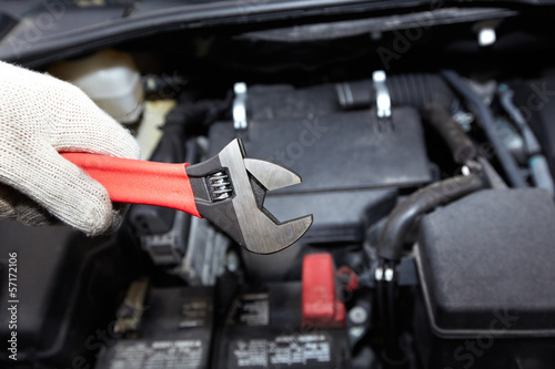 Hands of auto mechanic with wrench.
