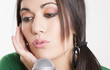 Performer Female Sings Into Microphone Holding Ear Closed Listen