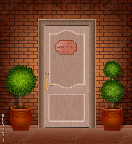 "Front door with a sign ""Welcome"" and trees in pots"
