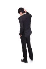 Rear view of young business man confused