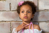 Portrait of a pretty little girl mulatto. Thoughtful lady.