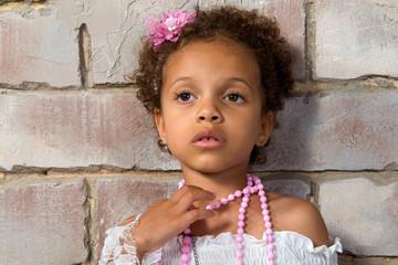 Portrait of a pretty little girl mulatto. Thoughtful lady.