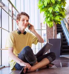 Handsome teenage boy talking by phone