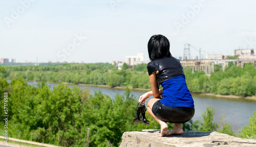 Young woman sitting on top of a stone