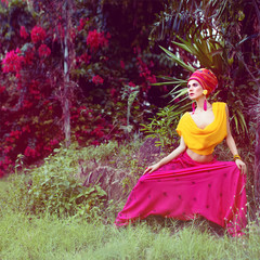 fashion portrait of a girl in a tropical jungle