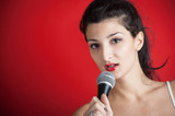 Beautiful girl singing with microphone against red background wi