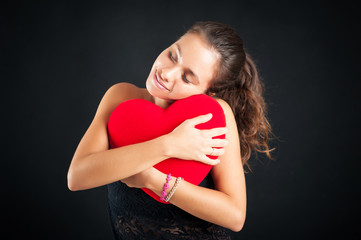 Portrait of attractive brunette woman hugging red heart against