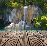 Waterfall and empty wooden deck table.