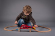 Young kid playing with train construction. Studio shot.