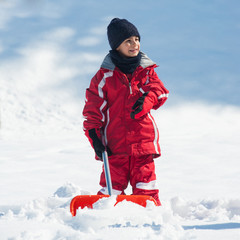 Young kid with shovel outdoors.