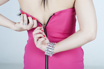 Woman fastening her pink dress with the zip
