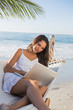 Brunette sitting on hammock using laptop