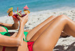 Sexy women taking sun clinking cocktails