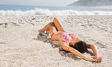 Sexy brown haired woman in pink bikini lying