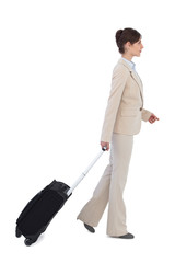 Serious businesswoman pulling suitcase