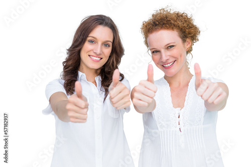 Two beautiful casual models posing with thumbs up