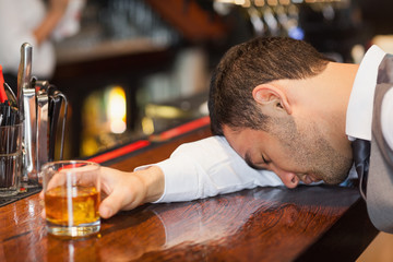 Drunk businessman lying on a counter