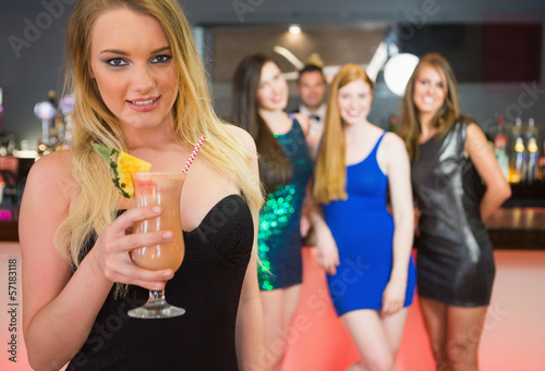 Blonde attractive woman holding cocktail standing in front of he