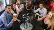 Young friends sitting together and raising their pints