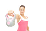 Smiling toned brunette showing grey and pink kettlebell