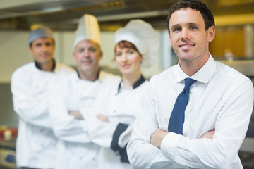 Young restaurant manager posing in front of team