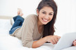 Woman uses tablet as she smiles looking straight ahead, while ly