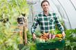 Proud man presenting vegetables in a basket