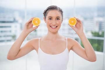 Happy healthy brunette holding orange slices