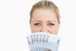 Woman hiding her mouth with her euros banknotes