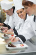 Team of chefs in a row garnishing dessert plates one girl smilin