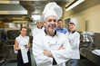 Head chef posing with team behind him