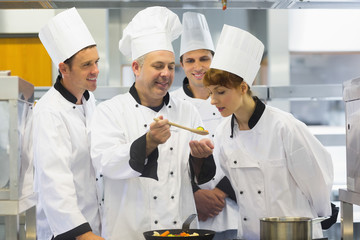 Senior chef showing food to his colleagues