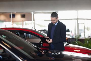 Man writing on a clipboard beside a car