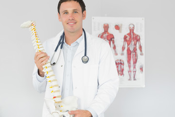 Handsome content doctor holding skeleton model