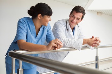 Doctor and nurse smiling and leaning against rail