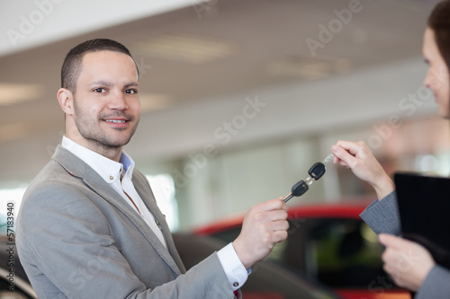 Man holding car keys with a businesswoman