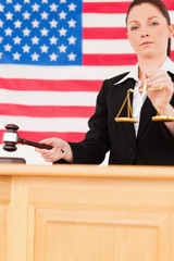Portrait of a young judge knocking a gavel and holding scales of