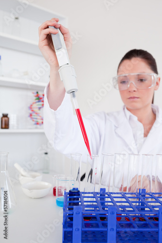 Good looking female biologist holding a manual pipette with samp