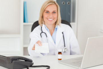 Smiling doctor holding prescription