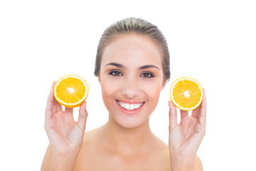 Smiling brunette woman holding two oranges halves