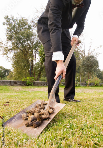 Businessman picking up droppings with a shovel