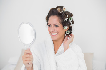 Cheerful natural brunette looking at mirror