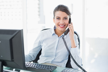 Cheerful classy brown haired businesswoman answering the telepho